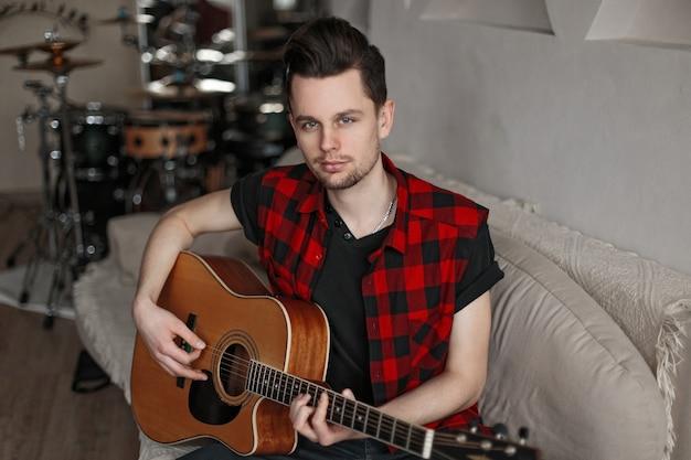 Przystojny młody mężczyzna w koszuli trzymając gitarę