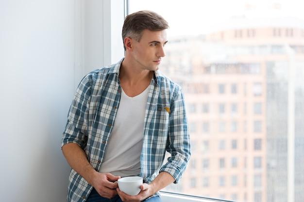 Przystojny młody mężczyzna w kraciastej koszuli siedzi na parapecie i pije kawę