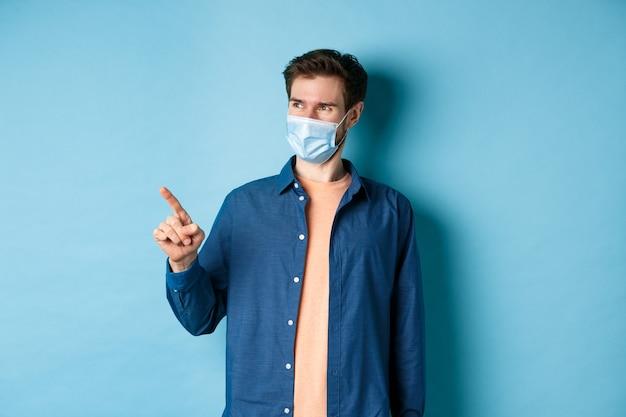 Przystojny młody mężczyzna w masce medycznej koronawirusa, wskazujący palcem w lewo i wyglądający na zadowolonego, uśmiechnięty do pustej przestrzeni, niebieskie tło.