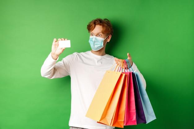 Przystojny młody mężczyzna w masce medycznej, pokazując plastikową kartę kredytową i torby na zakupy z przedmiotami zakupionymi ze zniżką, zielone tło.