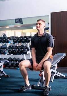 Przystojny młody mężczyzna w odzieży sportowej po krótkiej przerwie po treningu siedząc na siłowni