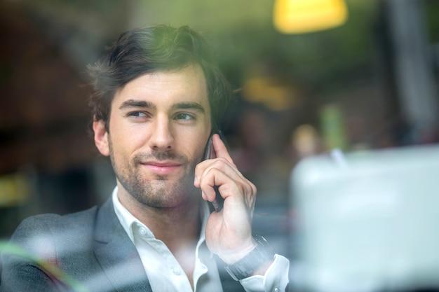 Przystojny młody mężczyzna w oknie