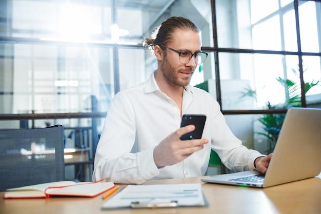 Przystojny młody mężczyzna w okularach, pracujący z laptopem i telefonem komórkowym, siedząc przy stole