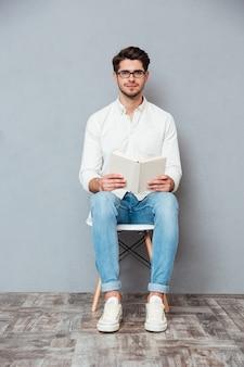 Przystojny młody mężczyzna w okularach siedzi na krześle i czyta książkę