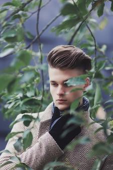 Przystojny młody mężczyzna w płaszczu na pozowanie w parku