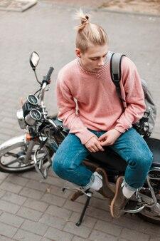 Przystojny młody mężczyzna w różowy sweter i niebieskie dżinsy z plecakiem i deskorolką siedzi na motocyklu