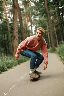 Przystojny młody mężczyzna w różowym swetrze jeździ na deskorolce