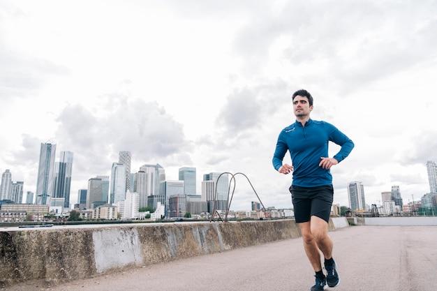 Przystojny młody mężczyzna w sportowej odzieży biegającej na zewnątrz z drapaczami chmur na tle
