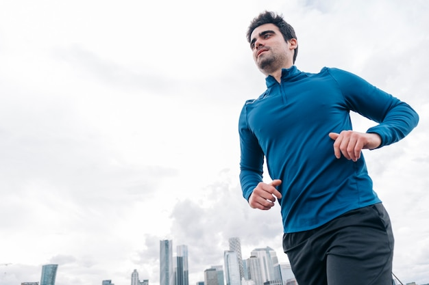 Przystojny młody mężczyzna w sportowej odzieży biegającej na zewnątrz z wieżowcami na tle