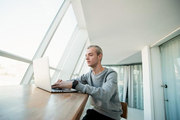 Przystojny młody mężczyzna w szarym dresie spogląda w ekran swojego komputera