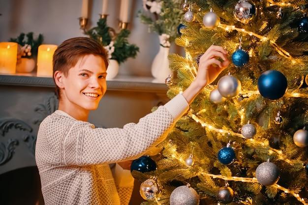 Przystojny młody mężczyzna wisi srebrną kulę na choince kolorowe ozdoby i jasne girlandy na choince...