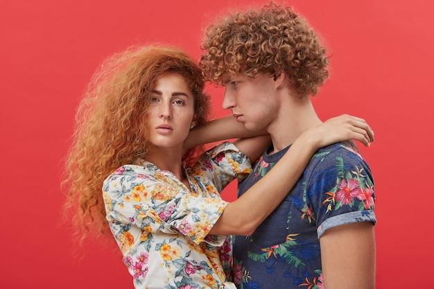Przystojny młody mężczyzna wpatruje się z podziwem w piękną dziewczynę o rudych włosach