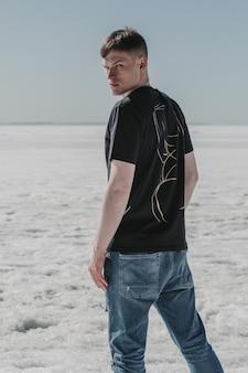 Przystojny młody mężczyzna wrócił do aparatu w czarnej koszulce i podartych dżinsach na zimną pogodę.