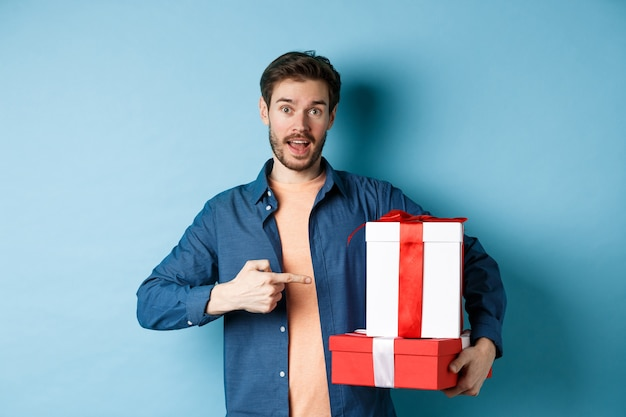 Przystojny młody mężczyzna, wskazując na pudełka na prezenty walentynki, stojąc na niebieskim tle w ubranie. skopiuj miejsce