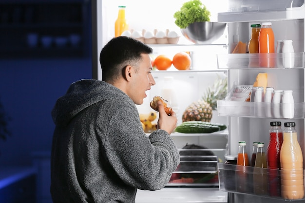 Przystojny młody mężczyzna wybierający jedzenie w lodówce w nocy