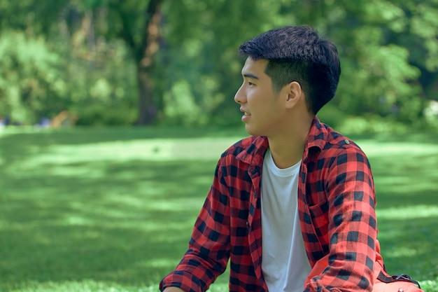Przystojny młody mężczyzna z azji siedzi latem na trawniku w parku.