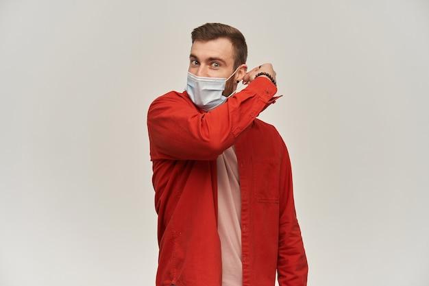 Przystojny młody mężczyzna z brodą w czerwonej koszuli próbuje zdjąć lub założyć higieniczną maskę w celu zapobiegania infekcji na białej ścianie