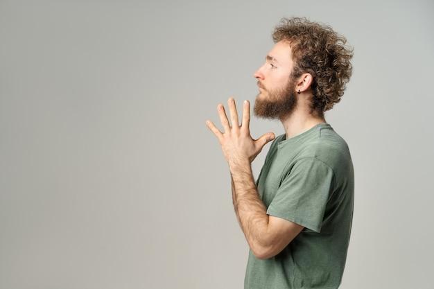 Przystojny młody mężczyzna z kręconymi włosami w oliwkowej koszulce patrząc z przodu na białym tle na białej ścianie.