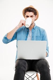 Przystojny młody mężczyzna z laptopem siedzi na krześle i pije kawę