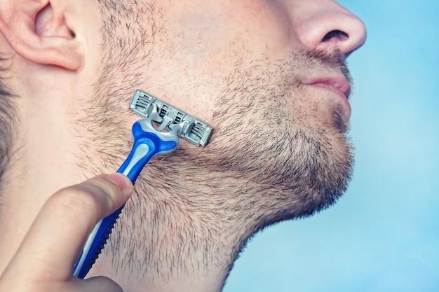 Przystojny młody mężczyzna z pianką na twarzy goli się brzytwą, na niebieskim tle. mężczyzna goli maszynką do golenia bez użycia pianki, mydła i kremu. golić się na sucho. makro, zbliżenie