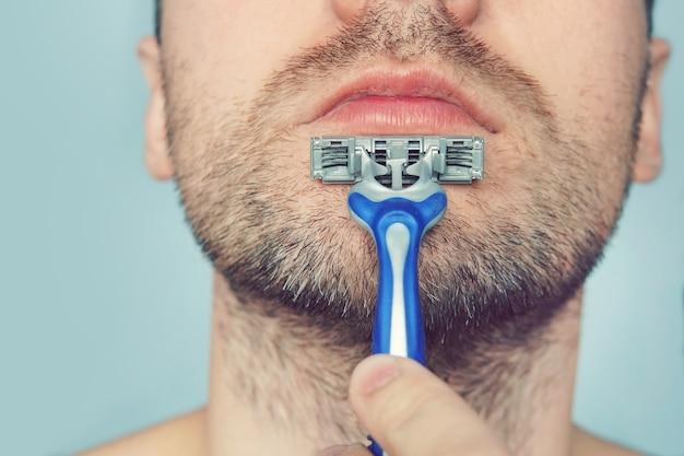 Przystojny młody mężczyzna z pianką na twarzy goli się brzytwą, na niebieskim tle. . mężczyzna goli maszynką do golenia bez użycia pianki, mydła i kremu. golić się na sucho.