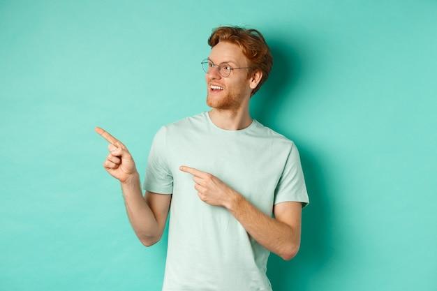 Przystojny młody mężczyzna z rudymi włosami i brodą, ubrany w okulary i t-shirt, wskazujący i patrzący w lewo z rozbawioną twarzą, sprawdzający reklamę na przestrzeni kopii, miętowe tło