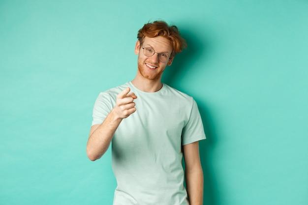 Przystojny młody mężczyzna z rudymi włosami, w okularach i t-shirt, wskazując palcem na aparat i uśmiechając się, wybierając cię, robiąc zaproszenie, stojąc na turkusowym tle.
