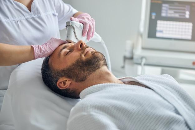 Przystojny młody mężczyzna z zamkniętymi oczami leżący na kanapie podczas laserowego zabiegu na twarz w centrum odnowy biologicznej