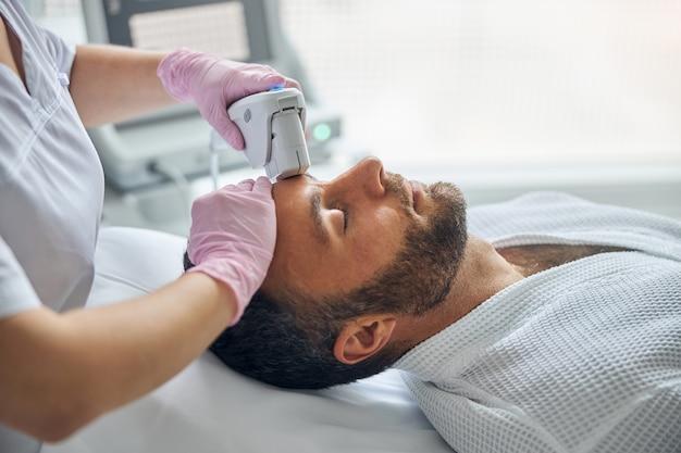Przystojny młody mężczyzna z zarostem leżący na kanapie podczas laserowego zabiegu na twarz w centrum odnowy biologicznej