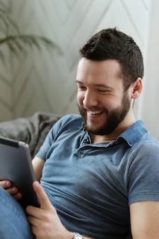 Przystojny młody mężczyzna za pomocą cyfrowego tabletu lub ebooka