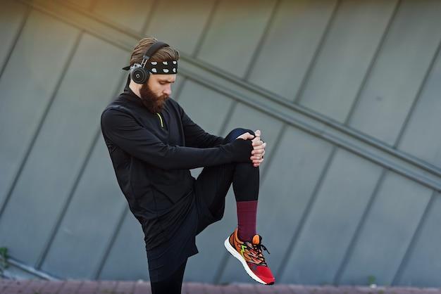 Przystojny młody mężczyzna ze słuchawkami robi ćwiczenia rozciągające i rozgrzewające przed bieganiem