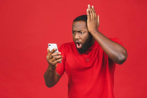 Przystojny młody mężczyzna, zszokowany, zaskoczony, szeroko otwarte usta, wściekły tym, co widzi na swoim telefonie komórkowym