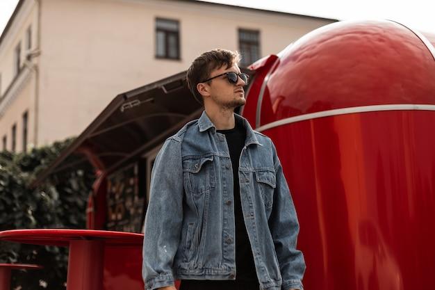 Przystojny młody model mężczyzna w niebieskiej stylowej kurtce dżinsowej w stylowych okularach przeciwsłonecznych pozuje w pobliżu czerwonego metalowego food trucka w mieście. hipster atrakcyjny facet spaceruje po ulicy w słoneczny letni dzień.
