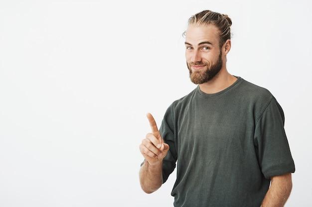 Przystojny młody modnisia mężczyzna wskazuje z palcem