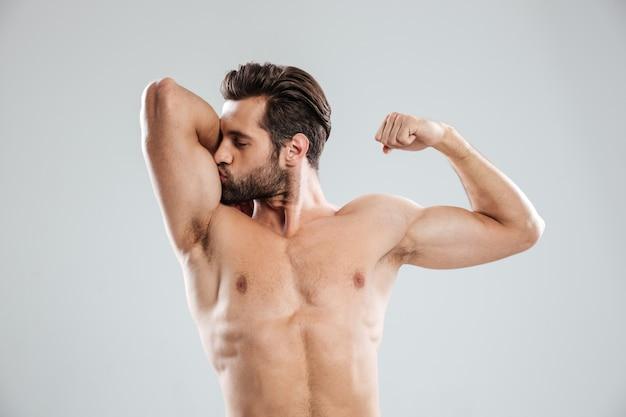Przystojny młody nagi mężczyzna pokazuje jego biceps i całuje