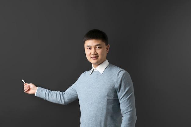 Przystojny młody nauczyciel azjatyckich na tle tablicy