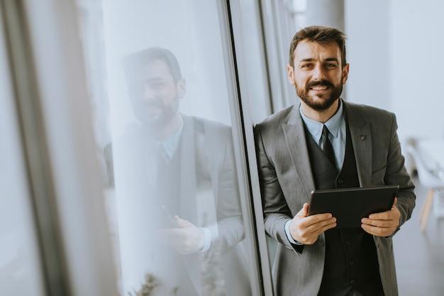 Przystojny młody nowoczesny biznesmen za pomocą cyfrowego tabletu w biurze