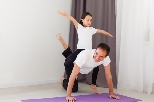 Przystojny młody ojciec i jego urocza córeczka robią deskę typu reverce z podnoszeniem nóg na podłodze w domu. rodzinny trening fitness.