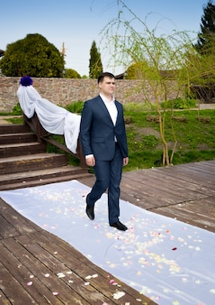 Przystojny młody pan młody spacerujący podczas ceremonii ślubnej z panną młodą