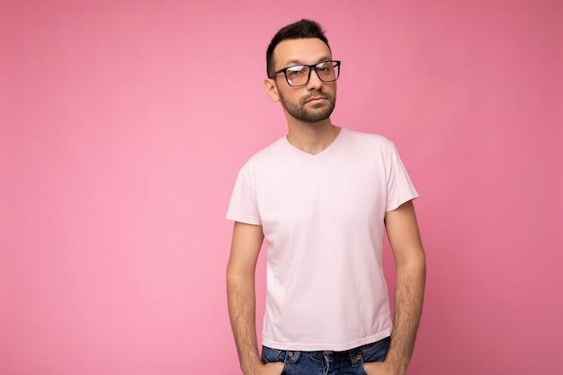 Przystojny młody pewny siebie brunet nieogolony mężczyzna ubrany w białą koszulkę na makietę i stylowe okulary optyczne