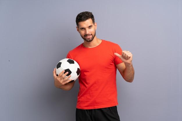 Przystojny młody piłkarz człowieka ponad pojedyncze białe ściany dumny i zadowolony z siebie