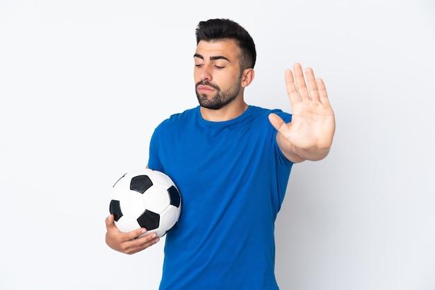 Przystojny młody piłkarz mężczyzna na odizolowanej ścianie robi gest stop i rozczarowany