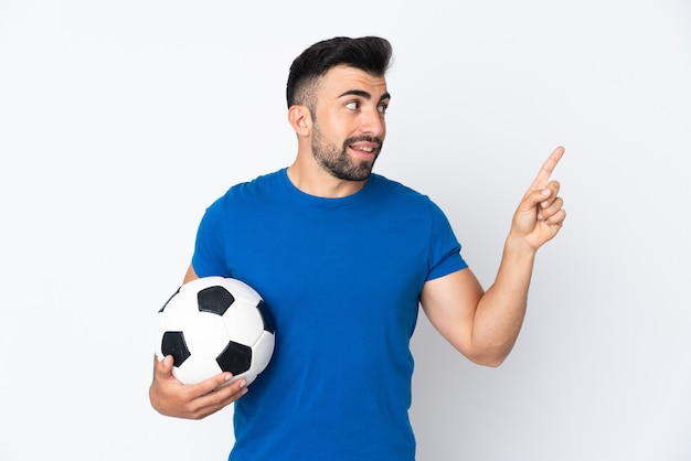 Przystojny młody piłkarz mężczyzna na odizolowanej ścianie wskazuje świetny pomysł