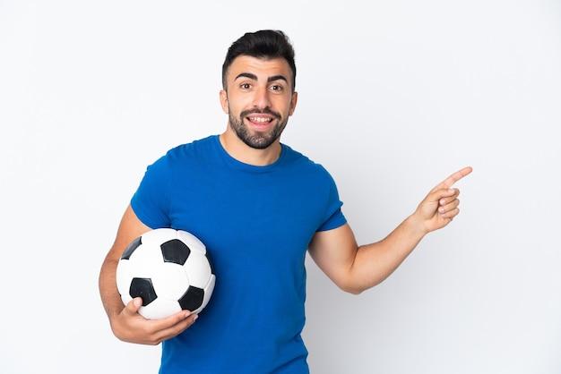 Przystojny młody piłkarz mężczyzna na pojedyncze ściany wskazując palcem na bok