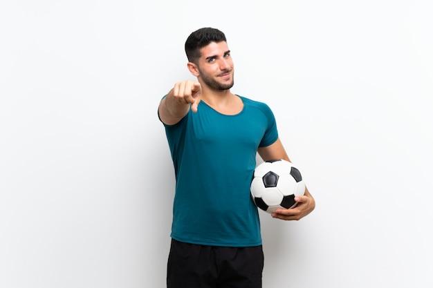 Przystojny młody piłkarza mężczyzna nad odosobnionymi białymi ściana punktami dotyka ciebie z ufnym wyrażeniem