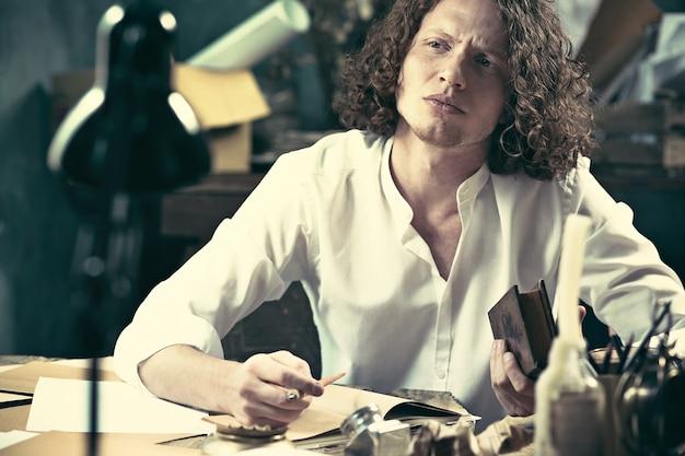 Przystojny, młody pisarz siedzi przy stole i pisze coś w swoim szkicowniku w domu