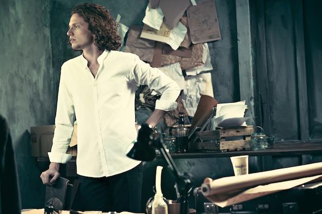 Przystojny młody pisarz stojący przy stole i zastanawiający się w domu