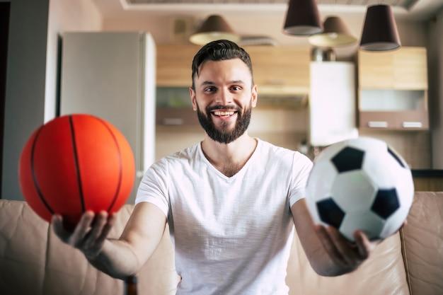 Przystojny młody podekscytowany nowoczesny brodaty mężczyzna relaksuje się na kanapie podczas oglądania meczu piłki nożnej w telewizji