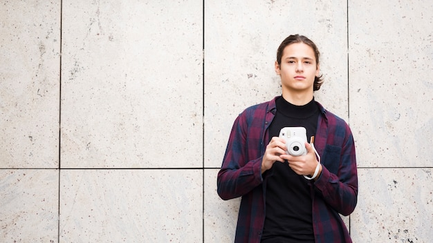 Przystojny młody podróżnik trzyma kamerę