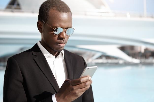Przystojny młody pracownik biurowy afroamerykanów w eleganckim czarnym garniturze i okularach stojący w miejskim otoczeniu, patrząc skoncentrowany, próbując zadzwonić po taksówkę za pomocą aplikacji online na swoim telefonie komórkowym
